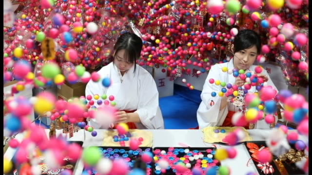 """miko"" female attendants at kinomiyajinja shrine in atami shizuoka prefecture can be seen making ""mayudama"" lucky charms for sale during upcoming new... - representing stock videos and b-roll footage"