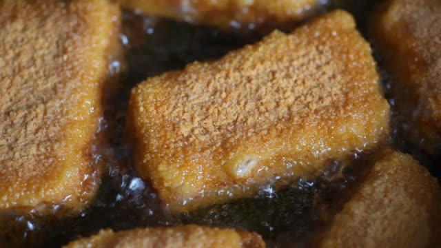 Milanese fish frying in pan