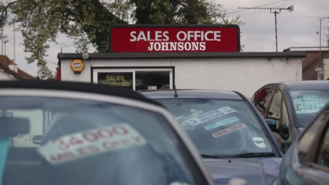 a mileage sticker sits in the window of a second hand car pull focus to 'sales office' sign at a used car dealership in leighonsea a price label and... - 売り出し中点の映像素材/bロール