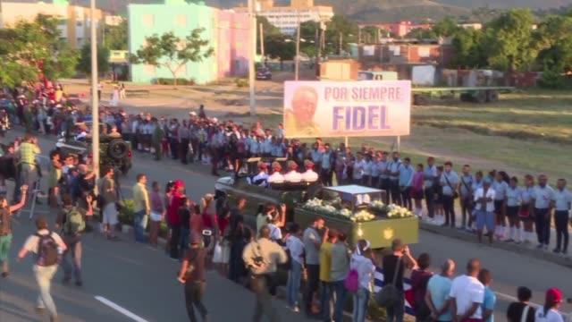vídeos de stock, filmes e b-roll de miles de cubanos se apostaron el domingo a la entrada del cementerio santa ifigenia en santiago de cuba para despedir por ultima vez a fidel castro... - hierro