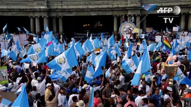 vídeos de stock e filmes b-roll de miles de guatemaltecos abarrotaron este sabado la plaza central de la capital para exigir la renuncia del presidente otto perez, senalado de liderar... - exigir