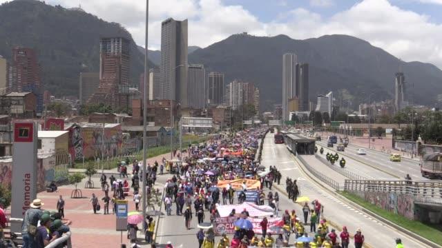 vídeos de stock e filmes b-roll de miles de maestros de la red de educacion publica de colombia en huelga desde hace dos semanas marcharon este miercoles por bogota para exigir mejoras... - exigir