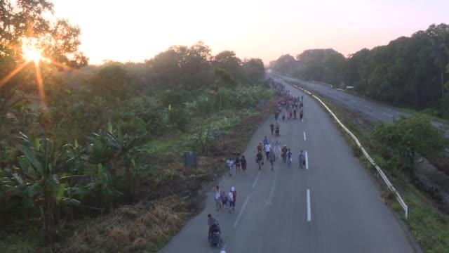 vídeos de stock, filmes e b-roll de miles de migrantes hondurenos que cruzan mexico en caravana reanudaron su marcha el miercoles decididos a llegar a estados unidos - convoy