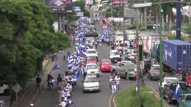 vídeos de stock e filmes b-roll de miles de nicaraguenses formaron el miercoles una cadena humana para exigir la salida del poder del presidente daniel ortega y el cese de la violencia... - exigir