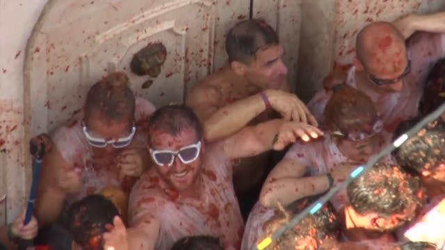 miles de personas participaron el miercoles en la tradicional batalla con tomates de la tomatina en el pueblo espanol de bunol - festival tradicional stock videos & royalty-free footage