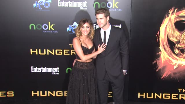 Miley Cyrus and Liam Hemsworth at The Hunger Games World Premiere on 3/12/2012 in Los Angeles CA