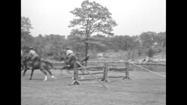 US Military Academy cadets galloping on horses and jumping fence / three shots of cadets on horses jumping fence / two shots of cadets galloping on...