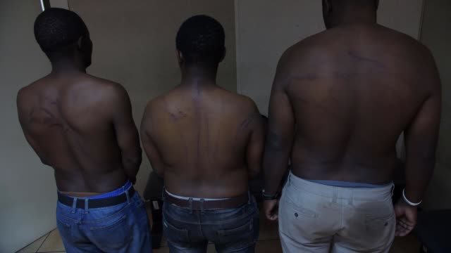 military accused of using 'systematic torture' to break up protests; zimbabwe: harare: int back view of three men standing with lacerations on their... - repubblica dello zimbabwe video stock e b–roll