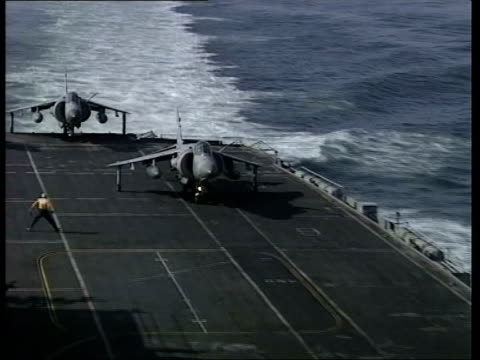 latest events; pool at sea: ext air view royal navy aircraft carrier hms illustrious at sea harrier aircraft along flight deck crew standing on... - forze armate britanniche video stock e b–roll