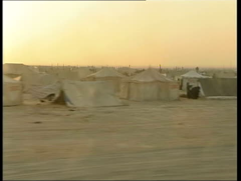 troops deployed/ allied casualties; lib afghanistan: ext tents of refugee camp track armed man in camp people seen next tents thru windblown sand - tent stock videos & royalty-free footage
