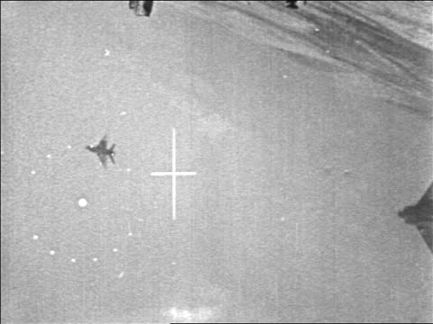 b/w 1967 military aircraft point of view thru crosshairs of fighter jet exploding in six day war / newsreel - sechstagekrieg stock-videos und b-roll-filmmaterial