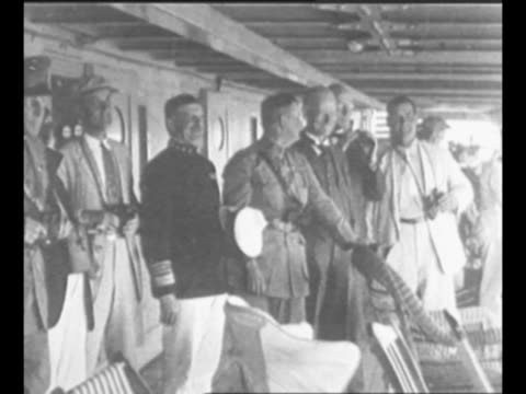 Military airplane flies drops bombs / 1921 military airplane flies / US Admiral Robert Coontz and foreign representatives stand on deck of ship and...