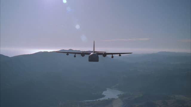 air to air, military airplane flying over hills - luftwaffe stock-videos und b-roll-filmmaterial