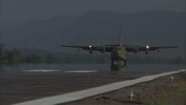 ms, pan, cu, military airplane landing on runway - luftwaffe stock-videos und b-roll-filmmaterial