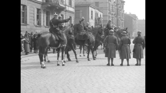 military and civilians mill about a cobblestone street as several mounted police arrive / erich von ludendorff gets out of an automobile with a woman... - 1920 stock-videos und b-roll-filmmaterial
