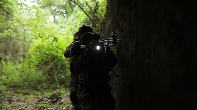 vidéos et rushes de forces armées militaires entrer dans le tunnel - lampe torche