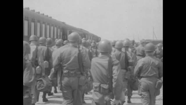military band plays in foreground as soldiers march alongside train as the us army's second division arrives / from behind group of soldiers walk... - 西ドイツ点の映像素材/bロール
