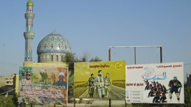 military billboards in baghdad, mosque and minaret in background - baghdad stock videos & royalty-free footage