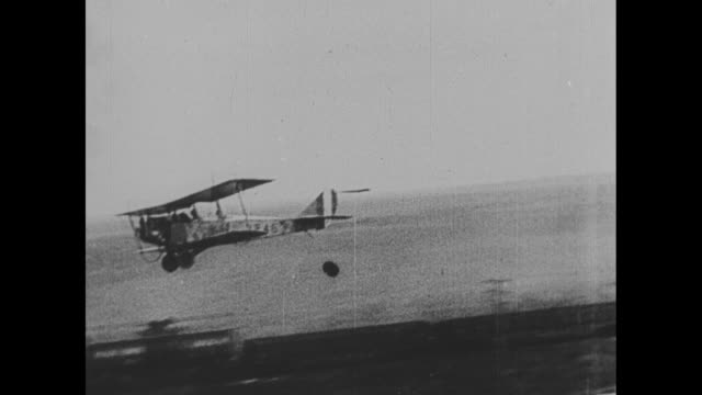 vidéos et rushes de military biplane flies low, dropping bomb near moving train / explosion near, but not on, the train / squadron of planes flies in formation /... - biplan