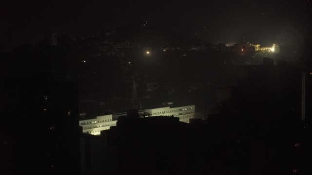 military building only building with electricity during blackout in caracas venezuela pot banging protest heard in background - power cut stock videos & royalty-free footage