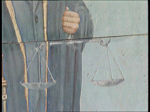 Portrait of Saddam Hussein painted on wall DOWN to his hand holding scales of justice Statue of Hussein holding pistol carved out of stone