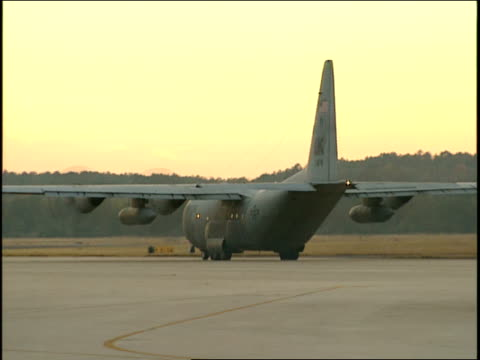 a military c-130 aircraft taxis on a runway before takeoff. - authority stock-videos und b-roll-filmmaterial