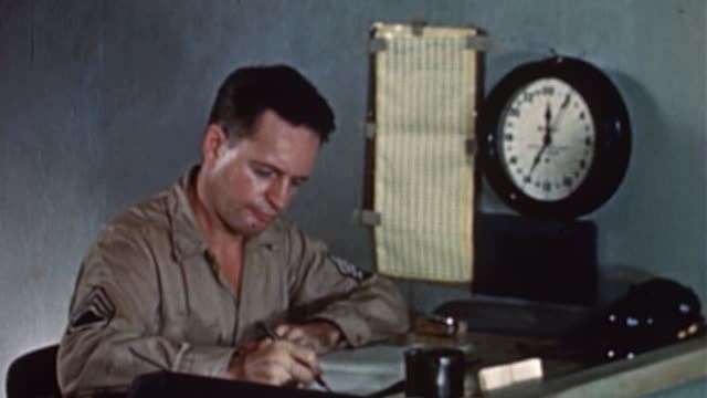 S  military clerks at work in command center, sitting at