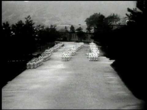 stockvideo's en b-roll-footage met military college parade ground w/ men in white uniforms. int classroom w/ professor fg. another classroom w/ military hats hanging outside wall,... - 1936