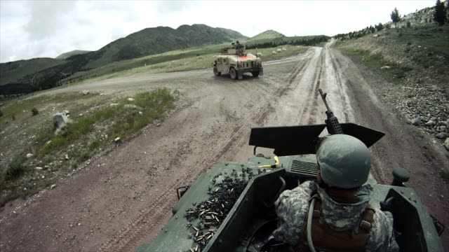 Military convoy approaches a hill