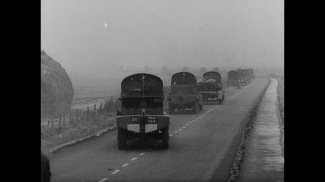b/w military convoy driving along misty country roads, beneath barrage balloons, past fields, big truck tires spinning / united kingdom - british military stock-videos und b-roll-filmmaterial