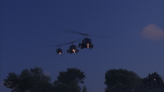 aerial, military convoy escorted by helicopters riding on bridge at night - suchscheinwerfer stock-videos und b-roll-filmmaterial