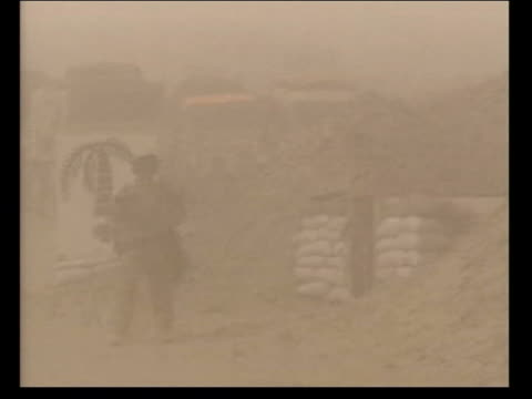 military countdown to war kuwait gv flag blowing on top of tent during sandstorm soldiers along at base lbv soldier in camouflage along thru desert... - 2003 stock videos and b-roll footage