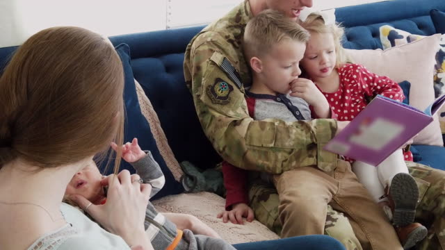 military dad with young family home during holidays enjoying time together - military stock videos & royalty-free footage