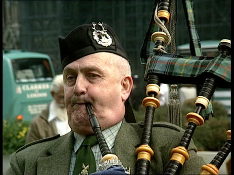 defence cuts **** rushes england london westminster lams men playing bagpipes outside parliament cms man playing bagpipes cms ditto ms bagpipe... - bagpipes stock videos & royalty-free footage