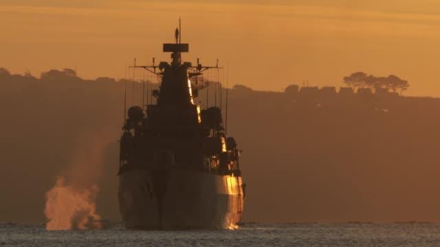 stockvideo's en b-roll-footage met militaire torpedojager aan de oceaan bij zonsondergang - british military