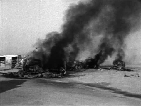 b/w 1967 military equipment burning in desert in six day war / newsreel - sechstagekrieg stock-videos und b-roll-filmmaterial