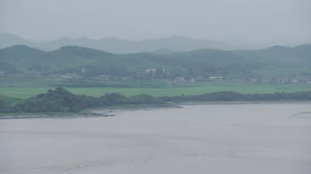 vídeos y material grabado en eventos de stock de military exercises continue in response to north korean threats south korea demilitarized zone up across river looking over to north korean border... - corea