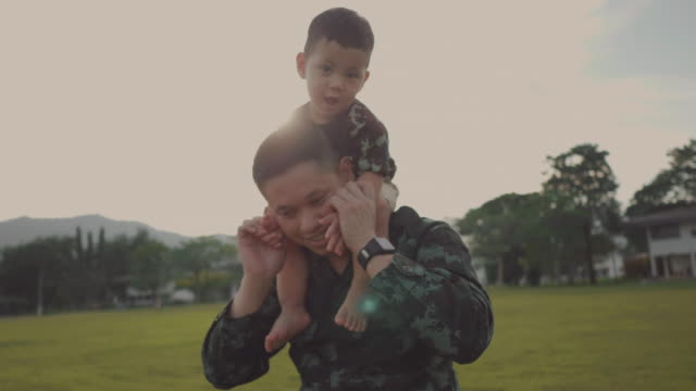 military father embraces his son in park - homecoming stock videos and b-roll footage