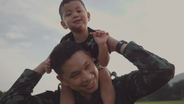 military father embraces his son in park - soldato video stock e b–roll