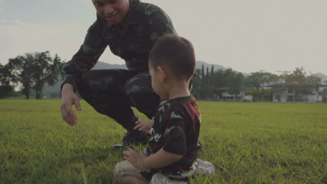 Military Father Embraces his Son in Park