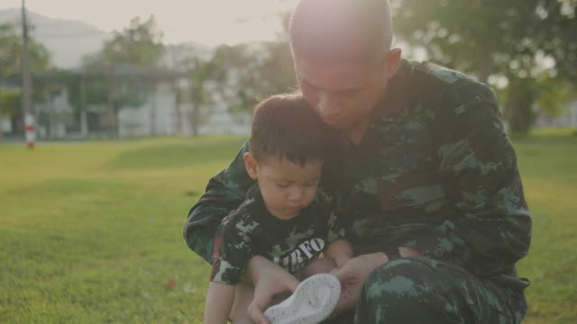 military father tying his son's shoelace in a park - marina personale militare video stock e b–roll