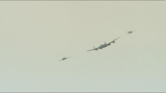 military flypast over beaches lancaster bomber and two spitfire aircraft group of veterans sit watching flypast - lancaster bomber stock videos & royalty-free footage