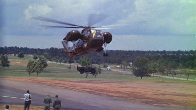 ms pan military helicopter depositing jeep on ground then landing - united states airforce stock-videos und b-roll-filmmaterial
