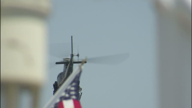 a military helicopter flies above waving american flags. - military helicopter stock videos and b-roll footage