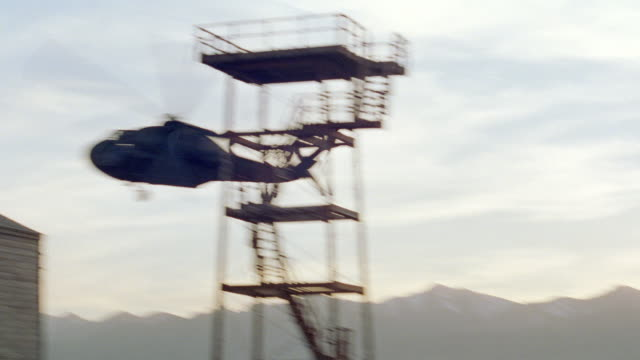 a military helicopter flies over a prison camp. - barracks stock videos & royalty-free footage