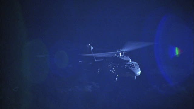 aerial, military helicopter flying against light over forest at night, usa - military helicopter stock videos and b-roll footage