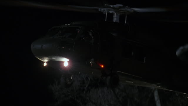 a military helicopter flying off into the sky at night. - military helicopter stock videos and b-roll footage