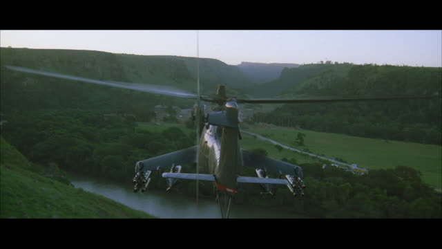 ws pov aerial military helicopter (mi-24) flying over camp under attack - military helicopter stock videos and b-roll footage