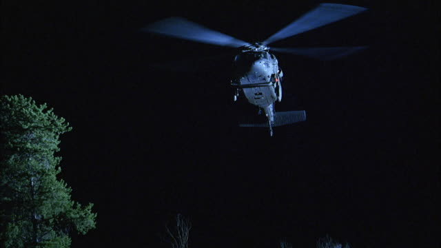 LA, MS, R/F, Military helicopter flying over forest at night, USA