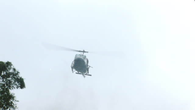 a military helicopter flying over smoky grasslands in vietnam. - vietnamkrieg stock-videos und b-roll-filmmaterial
